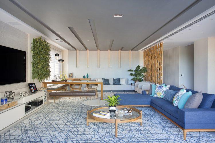 APARTAMENTO COM DÉCOR LEVE. Sala ampla com sofá azul, tapete azul e branco.