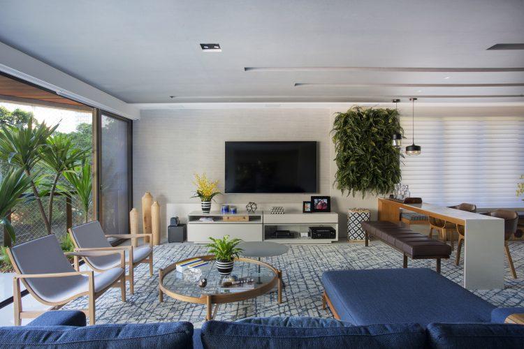 APARTAMENTO COM DÉCOR LEVE. Sala ampla e clara, Tv na parede, ao lado um retangulo de parede viva, com samambaias.