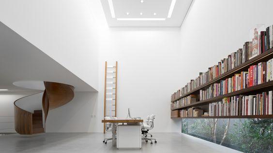 Lúdica e funcional, a magia das escadas helicoidais. Escada escultural em madeira dentro de um cubo branco, uma sala com pe direito alto