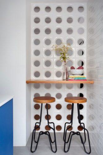 O cobogó é um elemento da arquitetura e design brasileiros. Elemento vazado criando uma divisão para recebr uma pequena bancada de alimentação.