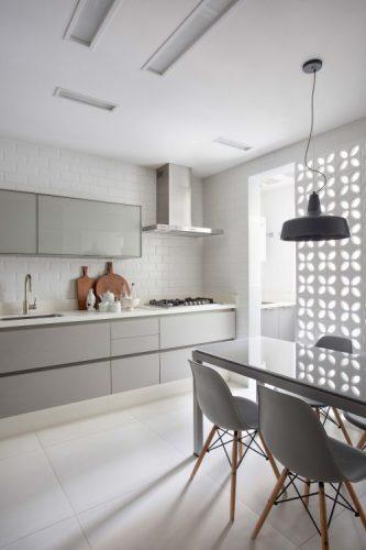 O cobogó é um elemento da arquitetura e design brasileiros. Na cor branca o elemento vazado ciando uma parede para separar a cozinha da area de serviço.