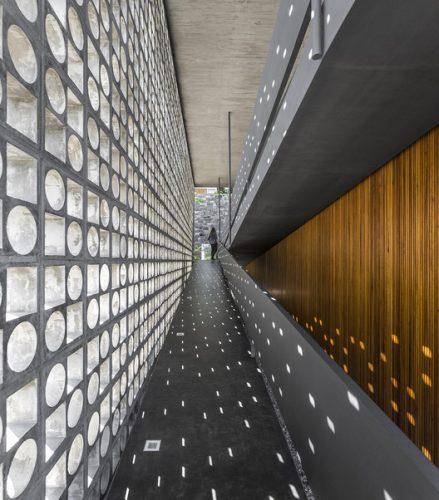 O cobogó é um elemento da arquitetura e design brasileiros. Corredor longo de uma casa com cobogos em uma lateral , criando sombras e luz