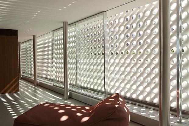 O cobogó é um elemento da arquitetura e design brasileiros. Fachada de um predio com cobogos visto aqui na parte de dentro, em uma sala criando lu e sombra