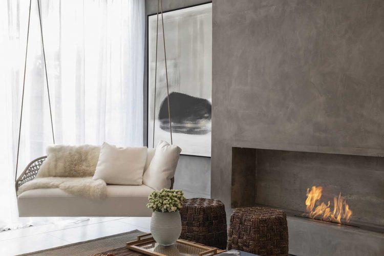 9 DICAS DE LAREIRAS ECOLÓGICAS. Sala com um balanço grande e ao lado uma parede de cimento queimado com um nicho para a lareira