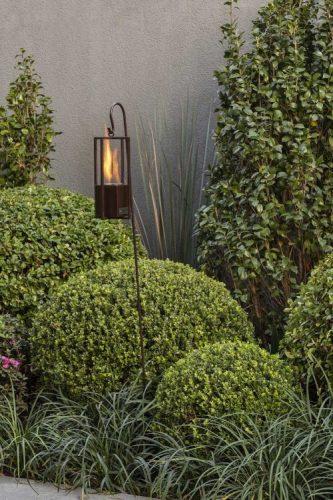 9 DICAS DE LAREIRAS ECOLÓGICAS. Jardim de buchinhos com uma tocha de mini lareira