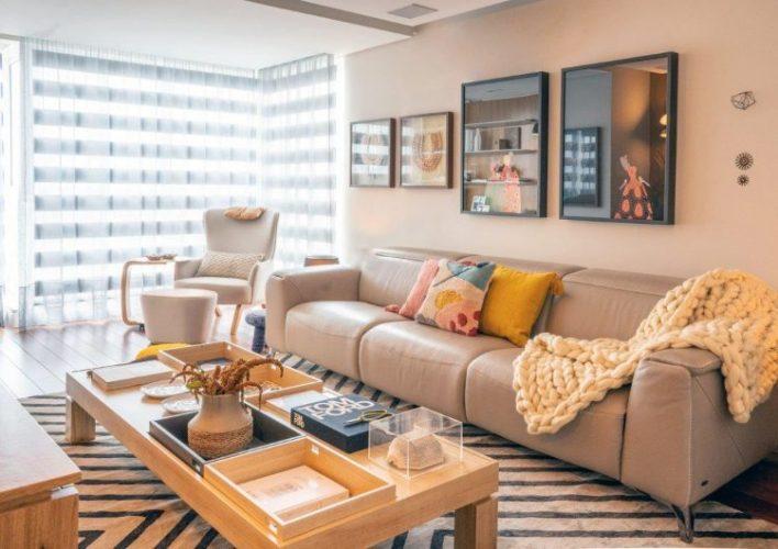 A reforma do imóvel, Francisco Beltrão, interior do Paraná, espaço da tv com sofá em couro claro e composição de quadros na parede
