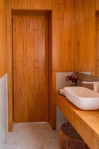 A reforma do imóvel, Francisco Beltrão, interior do Paraná, lavabo com bancada, porta e parede revestida em madeira freijó