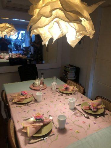 Foto de uma mesa posta com 4 lugares , toalha rosa e um lustre de papel em cima