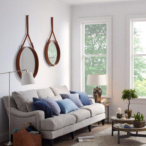 O espelho Adnet na decoração já virou um clássico. Dpis espelhos pendurados atras do sofá cinza. modelo redondo com alça de couro