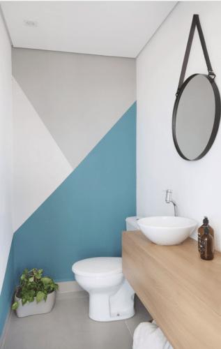 O espelho Adnet na decoração já virou um clássico, no lavabo com paredes pintadas com figuras geometricas