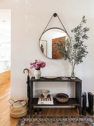 O espelho Adnet na decoração já virou um clássico, no hall de entrada em cima de um aparador