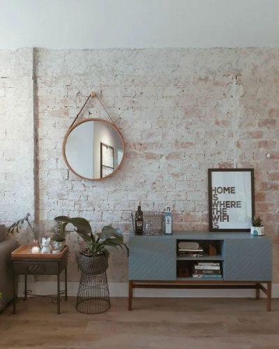 O espelho Adnet na decoração já virou um clássico, na parede de tijolinho