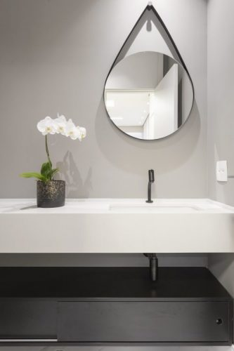O espelho Adnet na decoração já virou um clássico, no lavabo em cima da bancada branca