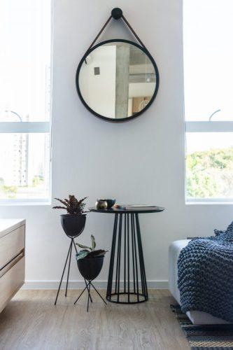 O espelho Adnet na decoração já virou um clássico, em cima de uma mesinha redonda