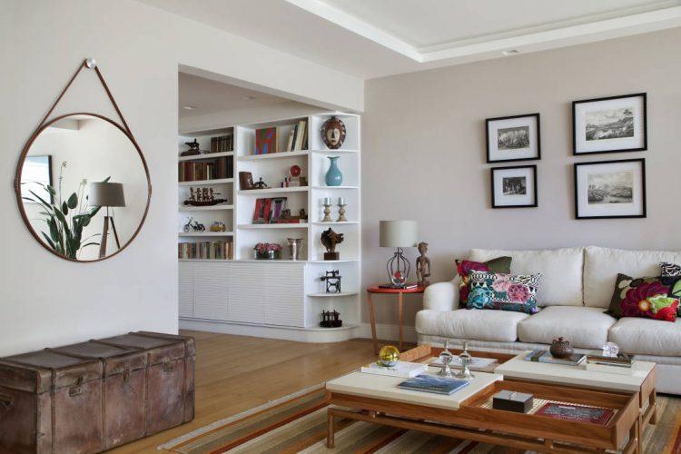 O espelho Adnet na decoração já virou um clássico, na sala ampla o espleho redondo com alça de couro pendurado em cima de um baú antigo