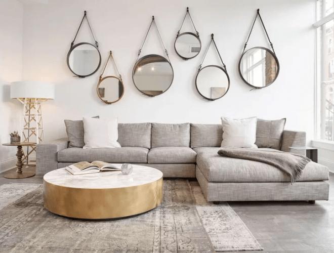 O espelho Adnet na decoração já virou um clássico. Na parede atras do sofá cinza em L, seis espelhos redondos com alça em couro pendurados na parede