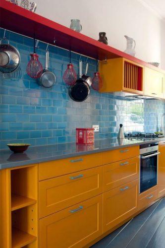 O poder das cores na decoração, cozinha com azulejos azuis, prateleira vermelha e armario amarelo