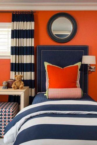 O poder das cores na decoração, quarto com parede laranja, cabeceira em azul jeans e cortina listrada de azul e branco