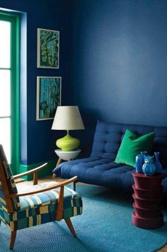 O poder das cores na decoração, sala com parede azul, sofá azul e janela pintada de verde.