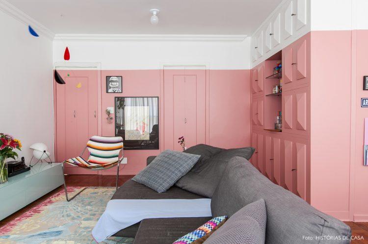 PAREDES EM DESTAQUE. Sala cm duas paredes em L pintadas de rosa, deixando apenas uma faixa larga na cor branca, perto do teto.