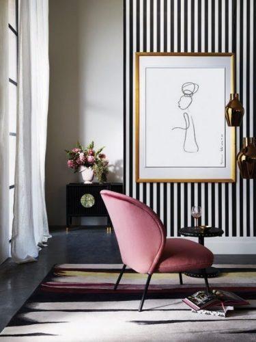 PAREDES EM DESTAQUE. Parede com papel de parede litsrado e preto e branco na sala, e na frente uma poltrona rosa