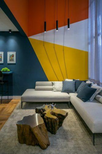 PAREDES EM DESTAQUE. Sala com um sofá em L e na aprede fundo uma pintura geometrica na cores azul , amarelo, vermelho e branco