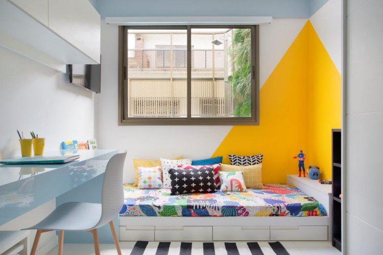 PAREDES EM DESTAQUE. Quarto de criança, cama baixa e na parede um triangulo pintado de amarelo formando uma especie de cabaninha