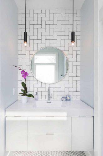 AZULEJO DE METRÔ: IDEIAS PARA SE INSPIRAR,na parede de fundo da bancada do banheiro, paginação espinha de peixe com rejunte preto, espelho redondo e bancada branca