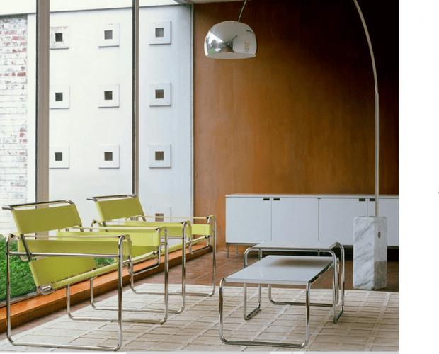 Cadeiras amarelas em couro uma mesa de centro branca na frete e uma luminaria de piso ao lado