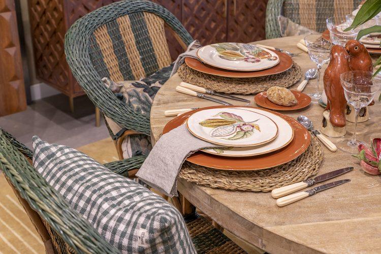 mesa posta com louca marrom o sousplat em palha, cadeiras em palha tambem