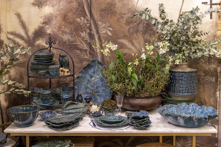 Loja de moveis e objetos decorativos. Mesa com louça azul no formato de folhas e saladeiras