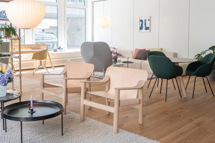 ambiente de loja com varios móveis, duas cadeiras com braço toda em couro claro, uma mesa redonda na frente