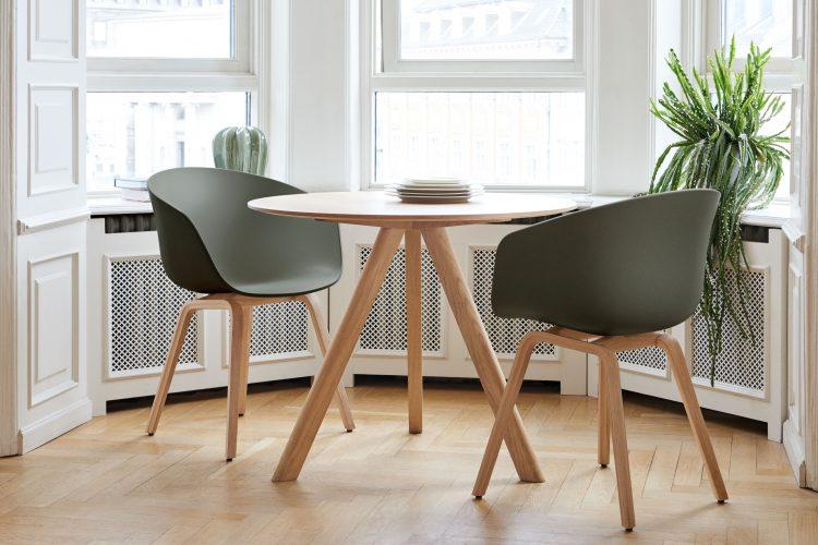 mesa redonda com duas cadeiras pretas com pés em madeira