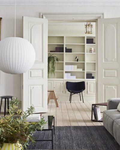 A marca dinamarquesa HAY chega ao Brasil. Sala com a porta aberta para outra e uma estante no fundo com uma cadeira preta na frente