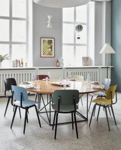 Moveis cm design dinamarques. Mesa redonda com tampo em madeira e cadeiras coloridas ao redor