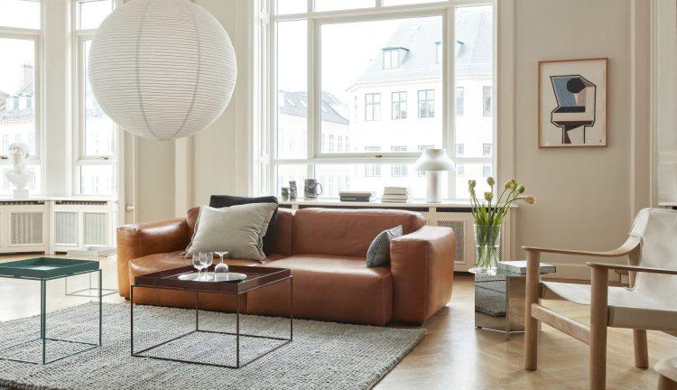 sala com amplas janelas, sofá em couro marrom e mesinha quadradas em frente