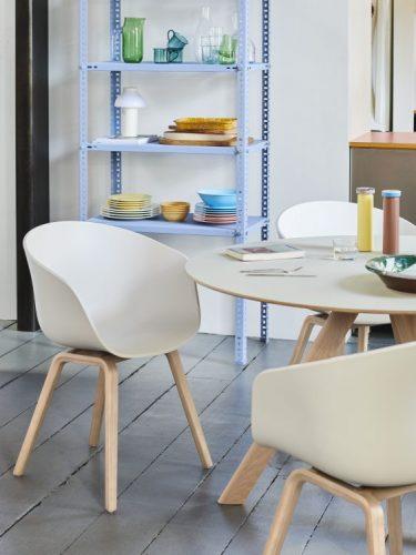 cdeira branca com pés em madeira e uma mesa redonda