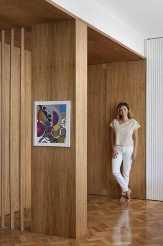 Hall de entrada revestido em madeira e a foto de uma mulher vestdo com roupas claras enconstada na parede