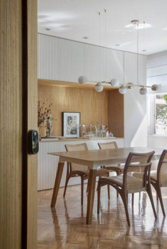 Mesa de jantar em madeira e na parede de fundo armarios ripados em madeira branca com um nicho grande no meio