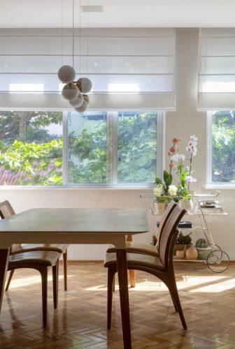 Aparatmento com janelas grandes, mesa de jnatar em madeira e carrinho de chá com flores em cima