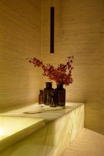 Lavabo com bancada em pedra onix , flores vermelhas e papel de parede bege em palhinha