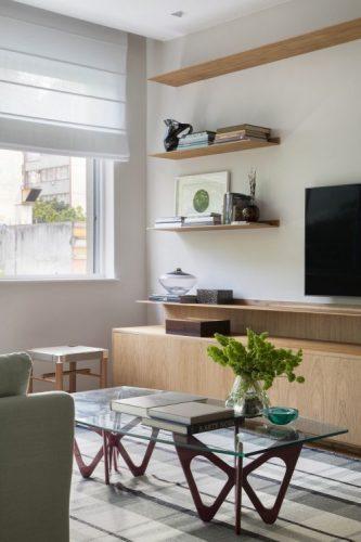 Mesa de centro com tampo em vidro e pés em madeira. Prateleiras em madeira na parede ao lado da tv