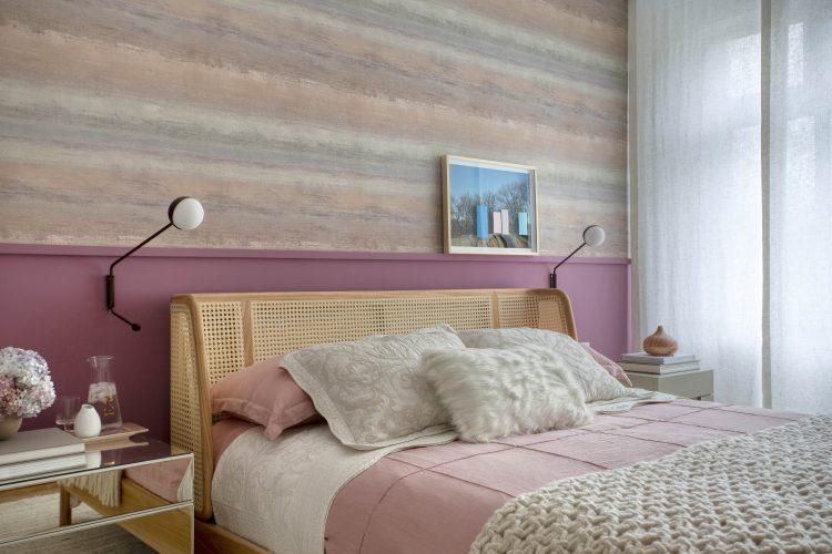 Quarto de casal com cabeceira em palinha, meia parede pintada de roxo .