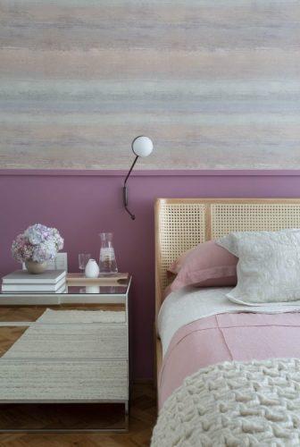 Quarto de casal com cabeceira em palinha, meia parede pintada de roxo