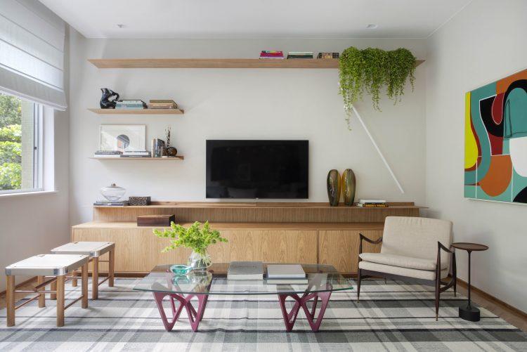 Sala em um apartamento em Ipanema, tv na parede , embixo um movel em madeira , mesa de centro e dois banquinhos