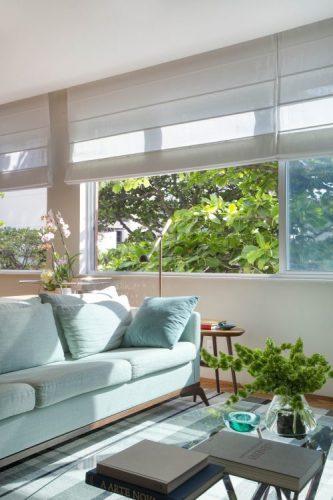 Sofá azul clarinho na sala com janelas grandes a bem claro