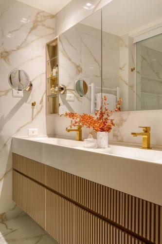Banheiro com bancada branca a armarios em madeira ripada