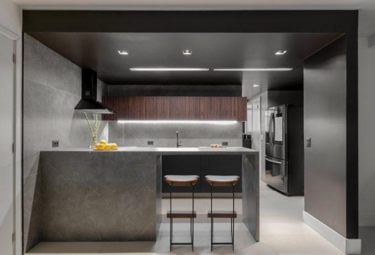 Cozinha aberta para sala, com bancada em cimento e duas banquetas em madeira. Armario superior em madeira e coifa preta