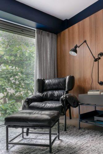 Apartamento no Leblon com décor minimalista e brutalista. Polrona em couro preto ao fundo parede revestida em madeira