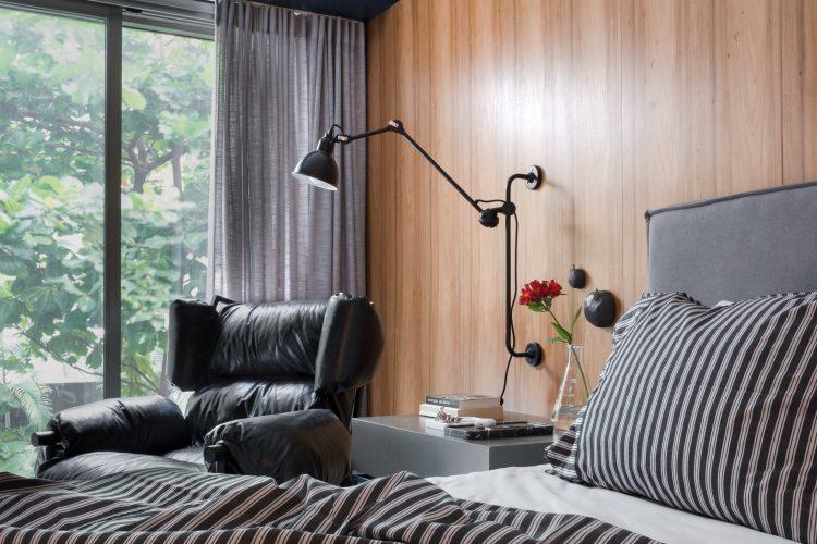 Quarto com parede de fundo da cama em madeira. cabeceira lisa em tecido e poltrona preta ao lado da cama